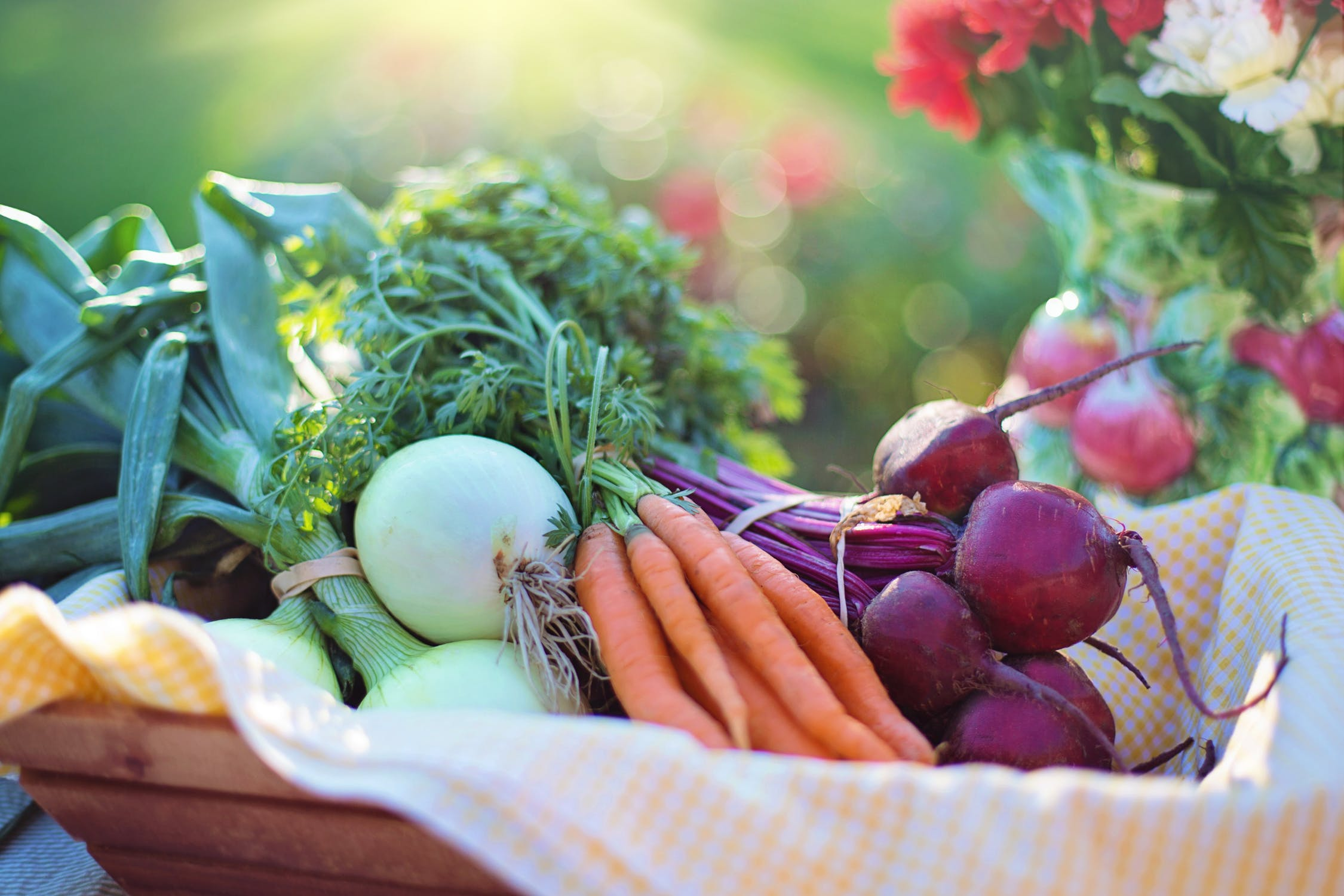 A basket of community garden vegetables: onions, beets, and carrots