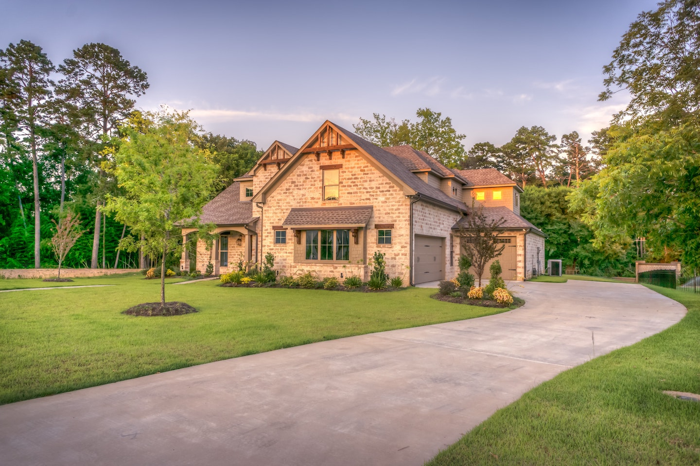 Beautiful stone house at dusk with green lawn